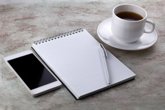 Coffe cup ,cel phone and notebook on a marble background