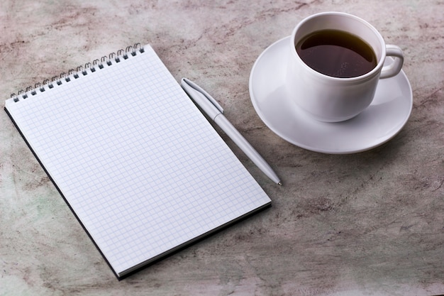 Coffe cup and notebook on a marble background