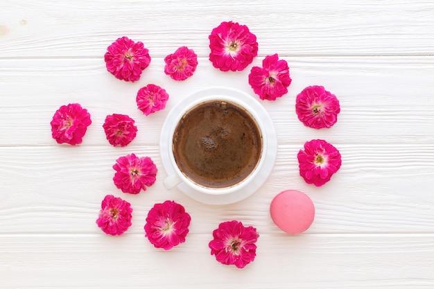 白い木製の背景にコーヒーカップのバラとピンクのマカロン