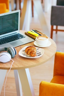Coffe,  laptop and croissants to show a business breakfast on the office table in morning