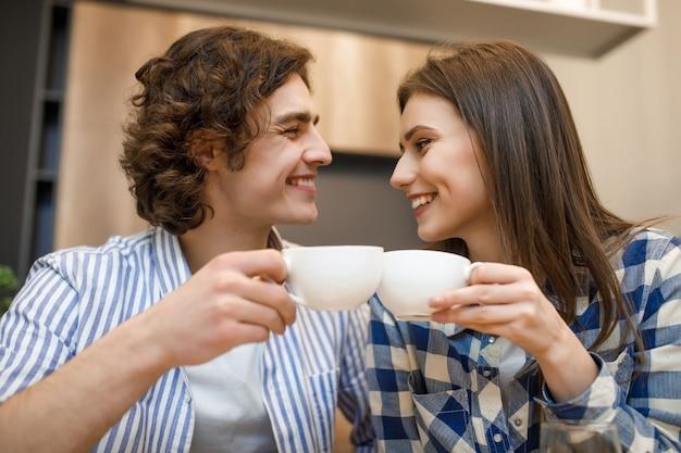 家でのコーヒータイム。ロマンチックな若いカップルがカップを持って、家庭の台所でコーヒーを飲む