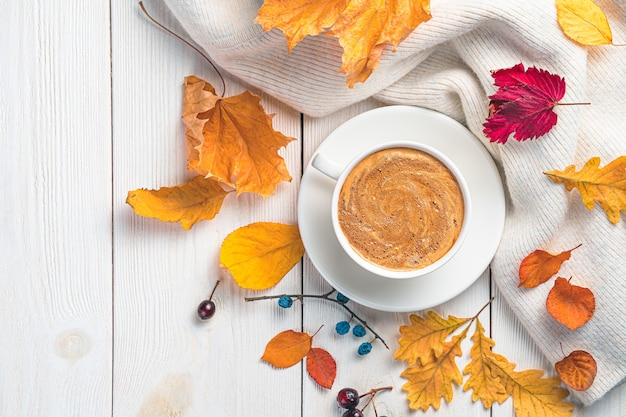 Кофе теплый свитер и осенние листья на белом фоне