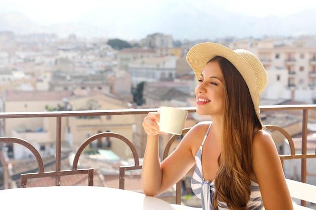 コーヒーの広告。美しい女性は、背景にイタリアの風景とカプチーノを取ります。広告用のスペースをコピーします。