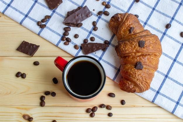 木製の背景にコーヒーとクロワッサン。上からの眺め。コーヒー豆