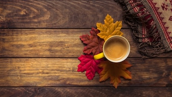 Coffee and autumn maple leaves composition