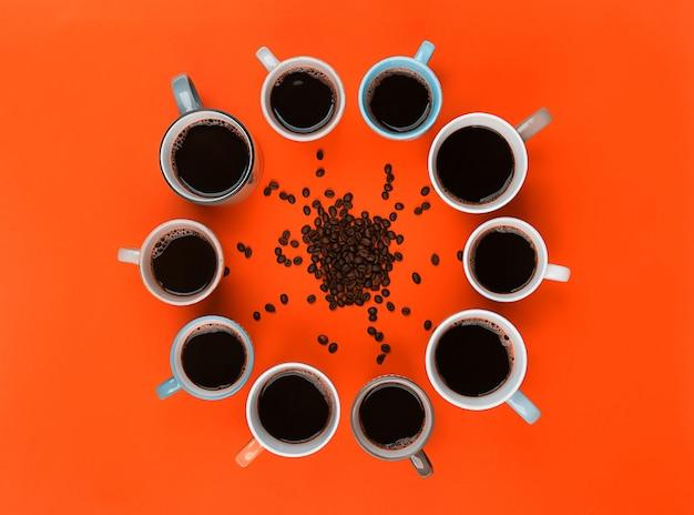 Кофе и бобы в разных чашках на ярко-оранжевом фоне