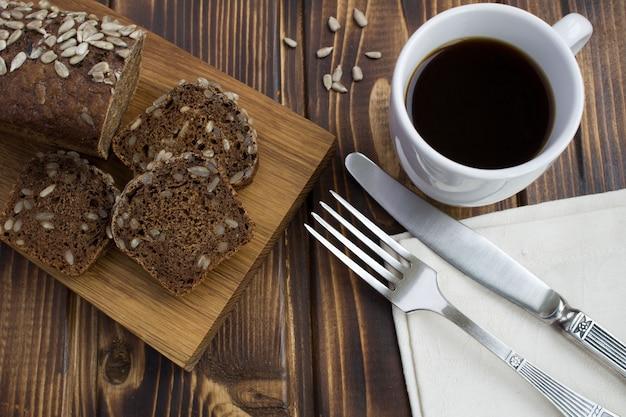 木の表面にヒマワリの種が入ったコーヒーとパン。上からの眺め。