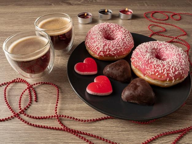 도넛과 하트 모양의 쿠키와 접시 앞의 테이블에 리본이 달린 접시 뒤에 커피와 촛불