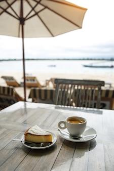 Кофе и чизкейк на столе.