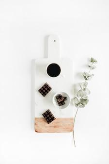 ユーカリの枝が付いたヴィンテージの大理石のまな板にコーヒーとチョコレート。フラットレイ、トップビュー