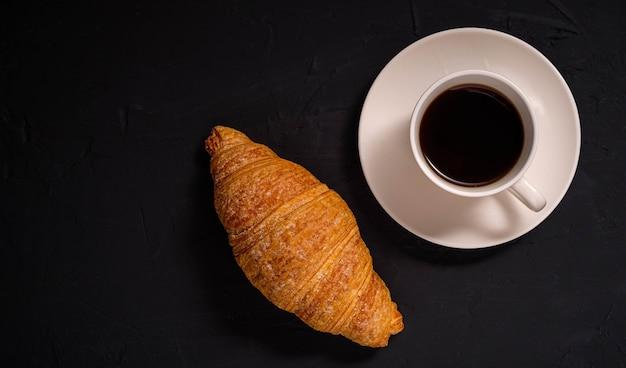 Кофе и круассан на темном фоне