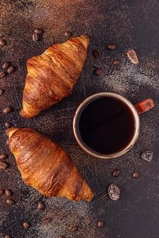 石の背景にコーヒーとクロワッサン。フランスの朝食。コピースペースのある上面図。