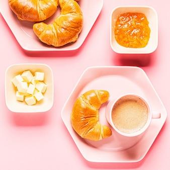 Кофе и круассаны на завтрак на розовом фоне, вид сверху,