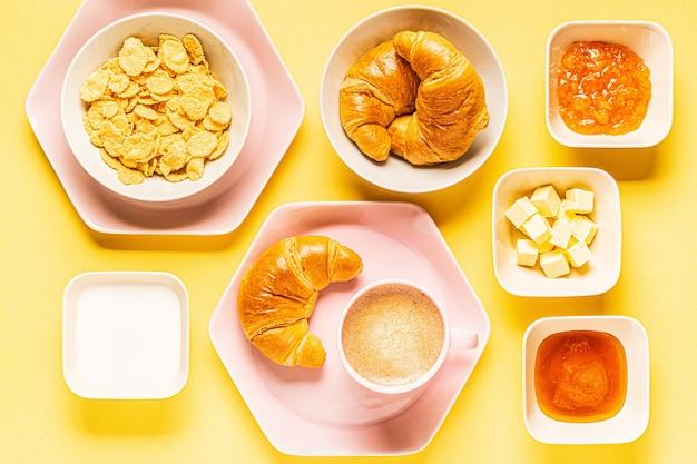 Кофе и круассаны на завтрак на желтом фоне, вид сверху,