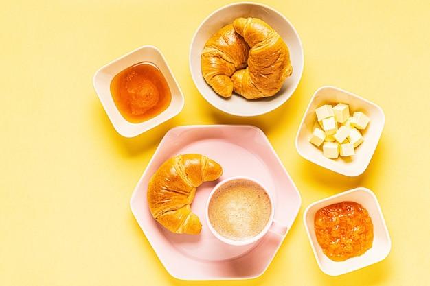 노란색 배경에 아침 커피와 크루아상