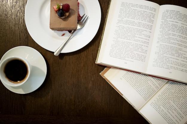 開かれた本の近くのコーヒーとデザート