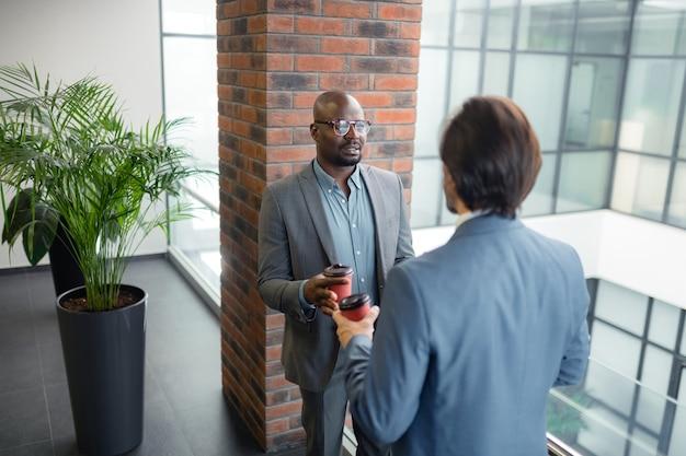 コーヒーとディスカッション。灰色のスーツを着て朝コーヒーを飲み、仕事について話し合う2人のビジネスパートナー