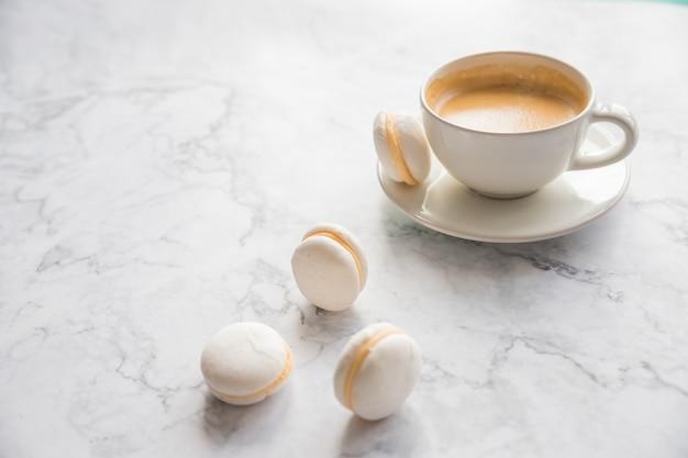 大理石の背景にコーヒーとフレンチマカロン。