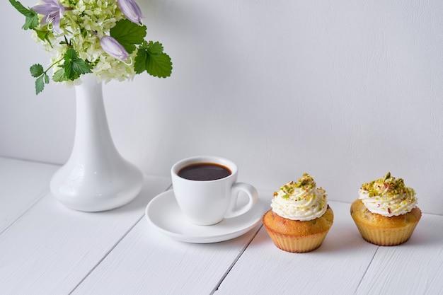 朝食用のコーヒーとフルーツのカップケーキ。白い木製のテーブルの上に花瓶にデザート、エスプレッソ、花と朝のテーブル。