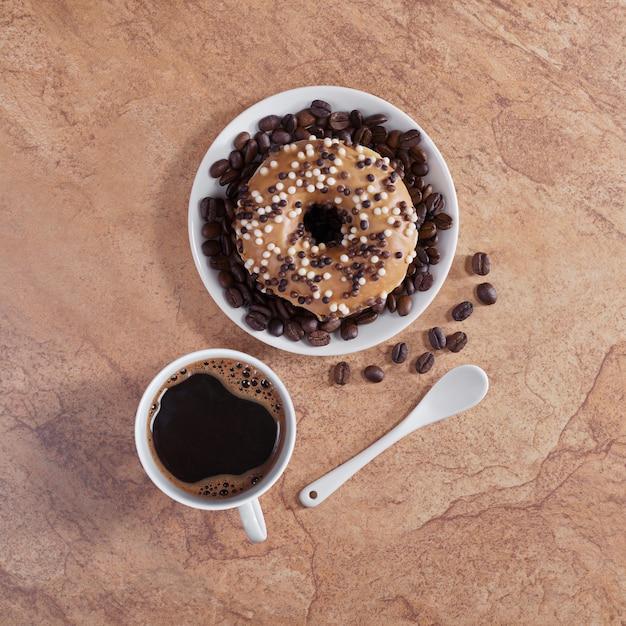 コーヒーと石のテーブルに艶をかけられたドーナツ