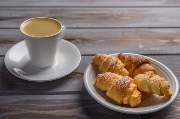 木製の表面の白いプレートにコーヒーと自家製クッキーのベーグル