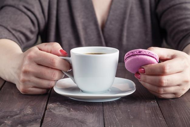 Кофе и макарон печенье на столе по утрам, женская рука держит чашку с горячим напитком