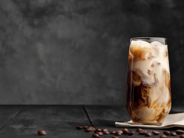 커피와 우유는 얼음과 함께 하이볼 잔에 섞여 있습니다. 회색 나무 테이블.