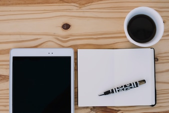 Coffee and notebook near tablet