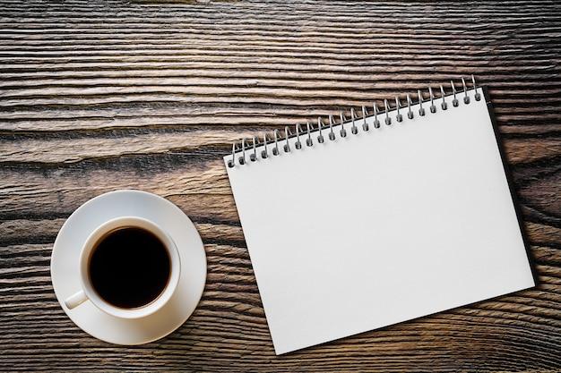 木製のテーブルの上のコーヒーとノート