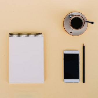Coffee and smartphone near notebook