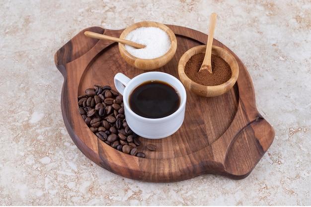 小さな木製トレイにコーヒーと砂糖