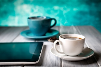 Coffee and tablet on the table Blue cup and background.