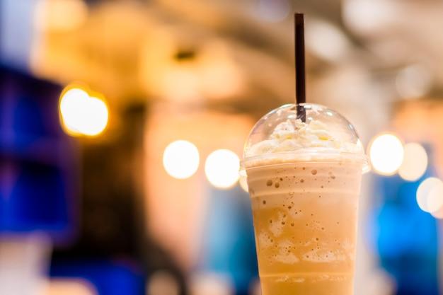 Кофе и взбитые сливки в стакане в магазине кафе с фоном боке.