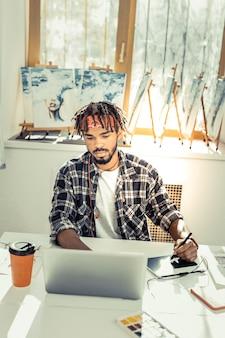 コーヒーと仕事。コーヒーを飲み、ラップトップに取り組んでいる若い創造的な才能のあるアーティスト