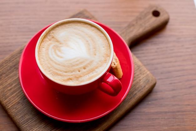コーヒーブレイク。古い木製の背景に美しいラテアートとカプチーノの赤カップ。赤いセラミックカップのラテアートcoffee.aromaコーヒー。カフェ、レストランでspace.woodテーブルをコピーします。
