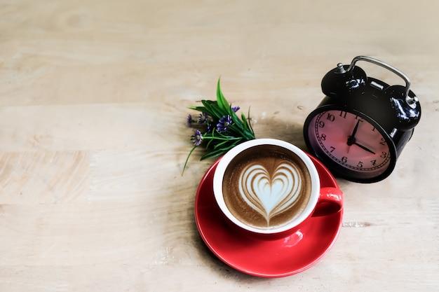 赤いカップの3時にコーヒーを、木製のテーブルに置いた紫の花束で