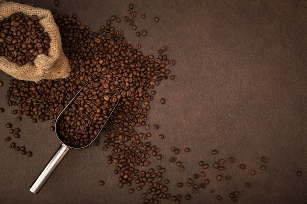 Coffee background. coffee beans, bag and scoop on brown background. top view copy space