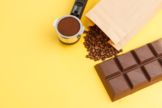 Coffee background. coffee in a holder, coffee beans, bar of chocolate