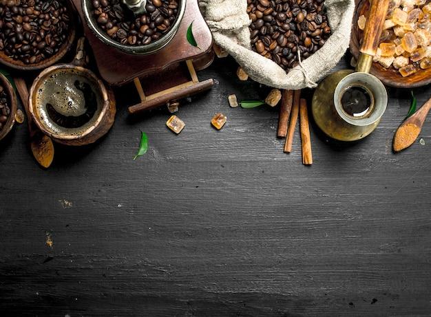 コーヒーの背景。砂糖の結晶とコーヒー豆が入った淹れたてのコーヒー。黒い黒板に。