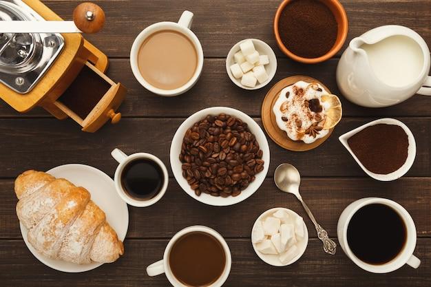 커피 배경입니다. 소박한 나무 테이블에 다양한 종류의 커피, 원두, 우유, 빈티지 그라인더, 달콤한 디저트 컵에 대한 최고의 전망