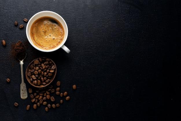 暗い背景にコーヒー豆、コーヒー、スプーンとコーヒーの背景。上からの眺め。コーヒーのコンセプト。