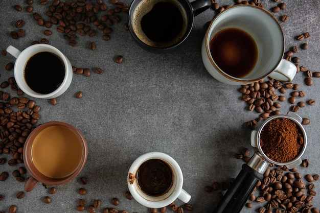 Кофейный фон с кофейными зернами, кофе и ложкой на темном фоне. вид сверху. концепция кофе.