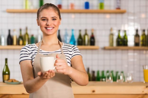 コーヒーバー。コーヒーバーで働いている間、笑顔でおいしいコーヒーで満たされたカップを保持している素敵なポジティブな若い女性