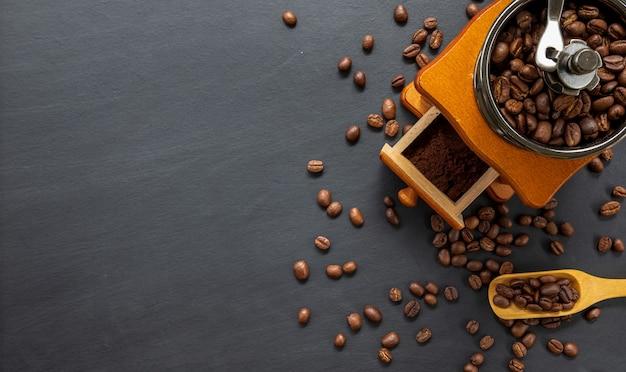 Кофейное зерно и ручная шлифовальная машина на черном фоне стола. место для текста. вид сверху