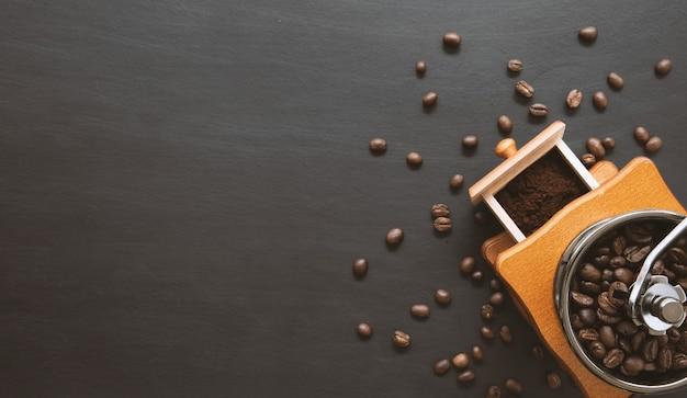 黒いテーブルの上のコーヒー豆とハンドグラインダー。テキスト用のスペース。
