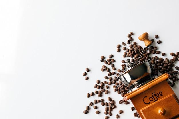 白いテーブルの上のコーヒー豆とハンドグラインダー。テキスト用のスペース。