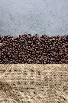 Кофе в зернах и мешок на старом фоне цемента