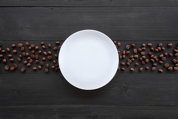 커피 나무와 검은 나무에 하얀 접시입니다. 평면도