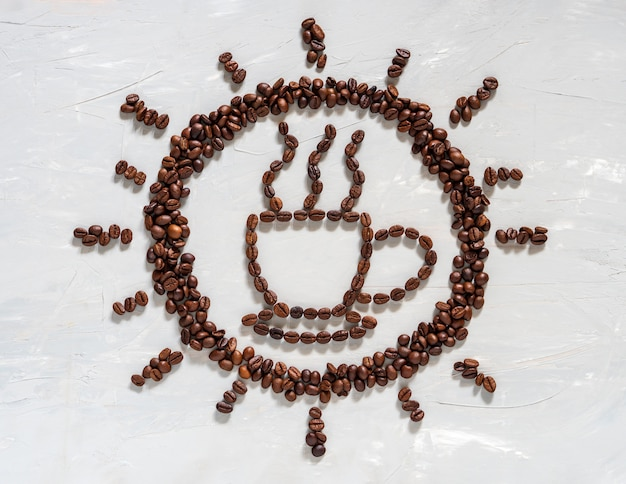Coffee bean in cup and sun shape on white floor