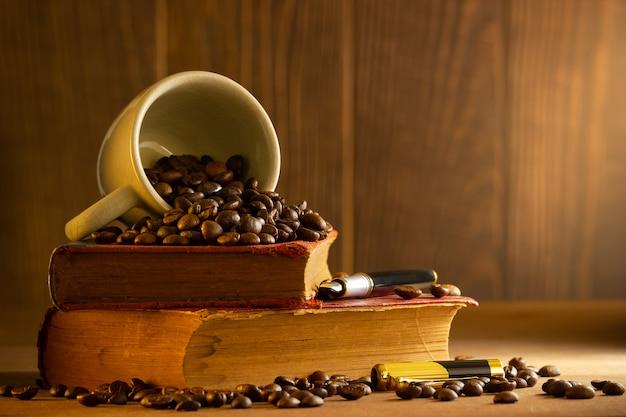 白いカップと朝の光の中で木製のテーブルの上にヴィンテージの本スタッキングでコーヒー豆。